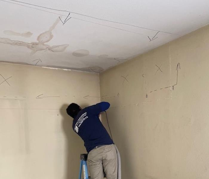 SERVPRO technicians using equipment on a wall with markings