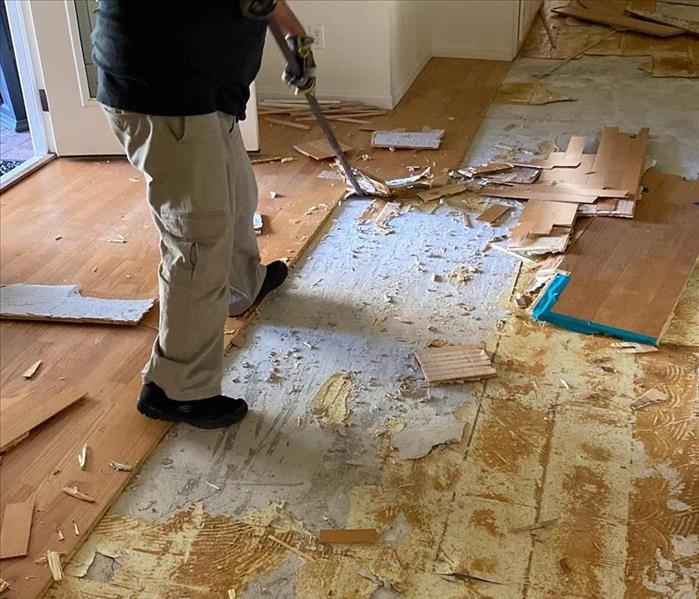 A man ripping wood flooring up.